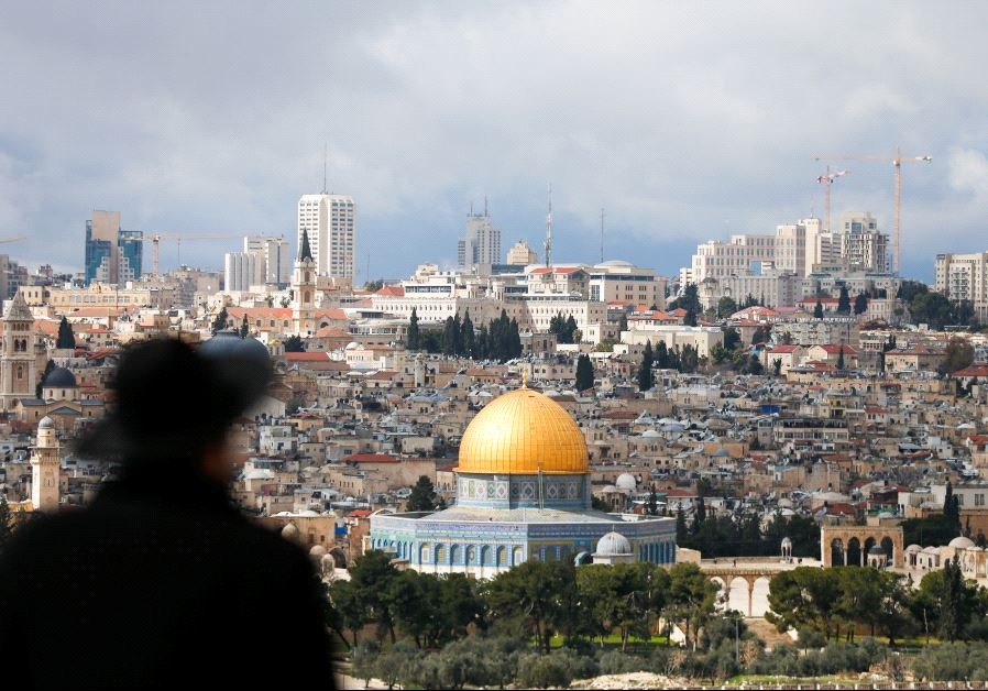Orthodox man stands facing the Dome of the Rock in Jerusalem