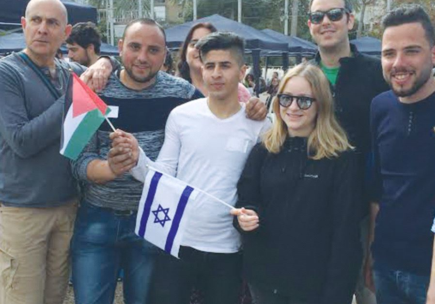 PEOPLE POSE for a photo at the Minds of Peace event in Tel Aviv on Friday.