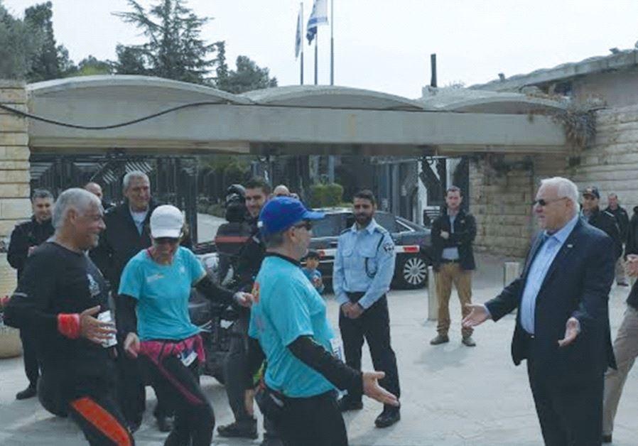 PRESIDENT REUVEN RIVLIN greets runners in the Jerusalem Marathon outside the President's Residence o