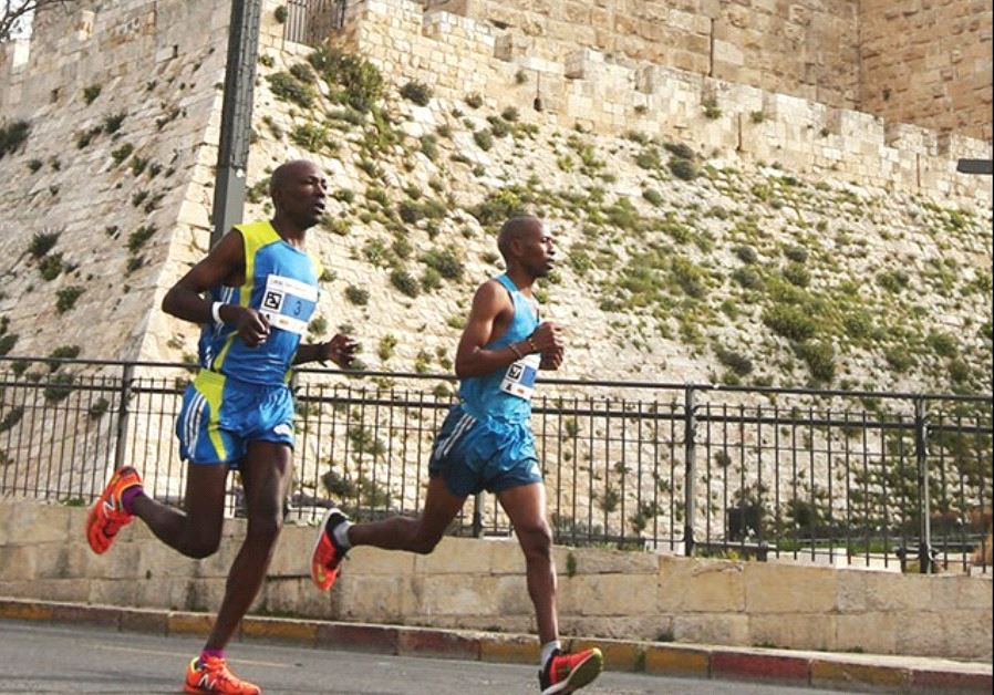 RUNNERS PASS by the walls of the capital's Old City during Friday's seventh annual running of the Je