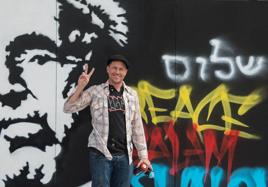 Graffiti artist and actor Corin Nemec stands by his creation at the Peres Center for Peace.
