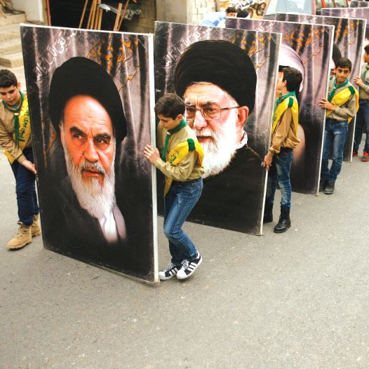 Hezbollah supporters carry portraits of the founder of Iran's Islamic Republic, Ayatollah Ruhollah Khomeini (left), and supreme leader Ayatollah Ali Khamenei, as they march in the southern Lebanese town of Kfar Hatta / AFP PHOTO