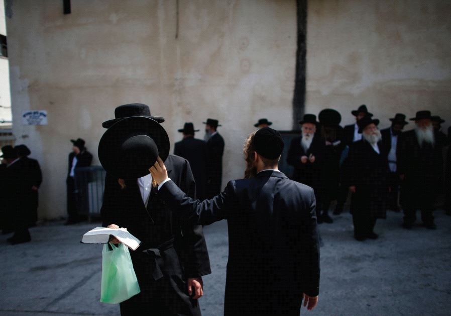 ULTRA-ORTHODOX MEN participate in a 2014 protest outside an IDF recruiting office in Jerusalem