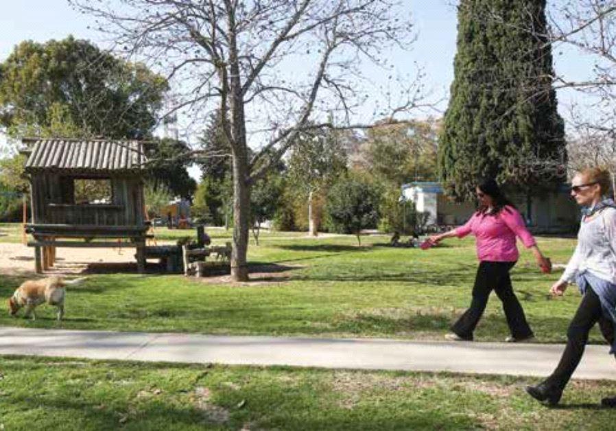 Nahal Oz resident Oshrit Sabag walks her dog in the Kibbutz earlier this month.