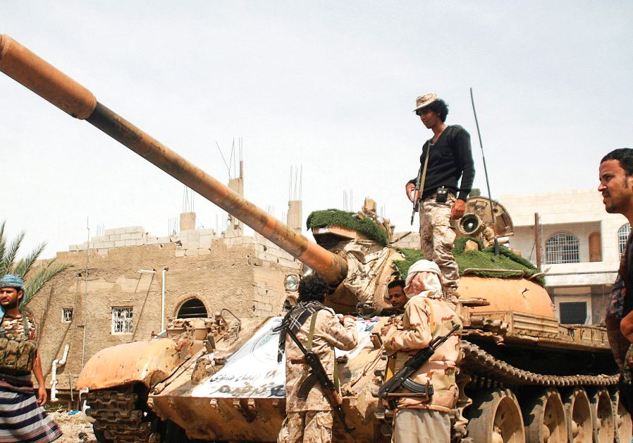 PRO-GOVERNMENT FIGHTERS gather next to a tank they use in the fighting against Houthi fighters in th