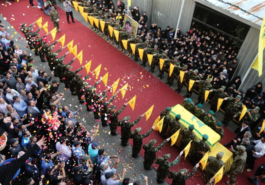 PEOPLE TOSS rose petals as Hezbollah members stand near the coffin of top Hezbollah commander Mustaf