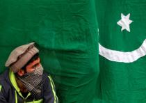 A masked protester sits next to a flag of Pakistan during an anti-Indian protest