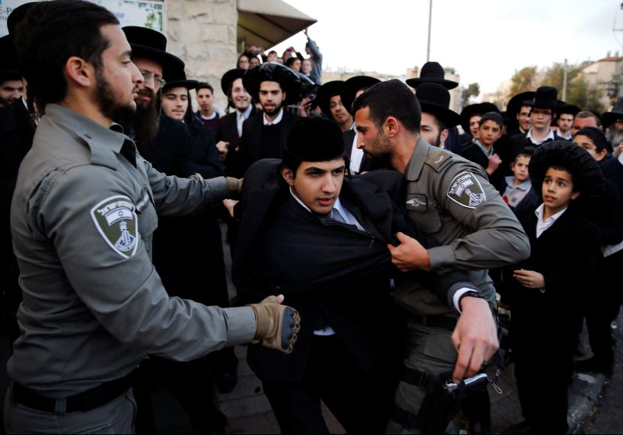 Ultra-Orthodox Jews take part in a demonstration against members of their community serving in the I