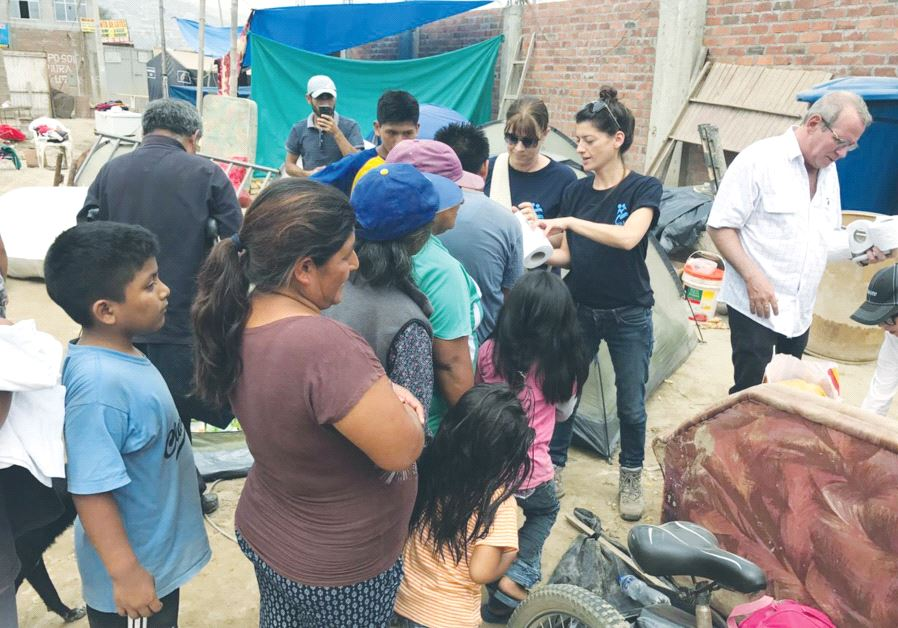 ISRAAID STAFF MEMBERS assist displaced residents in Lima last Friday.