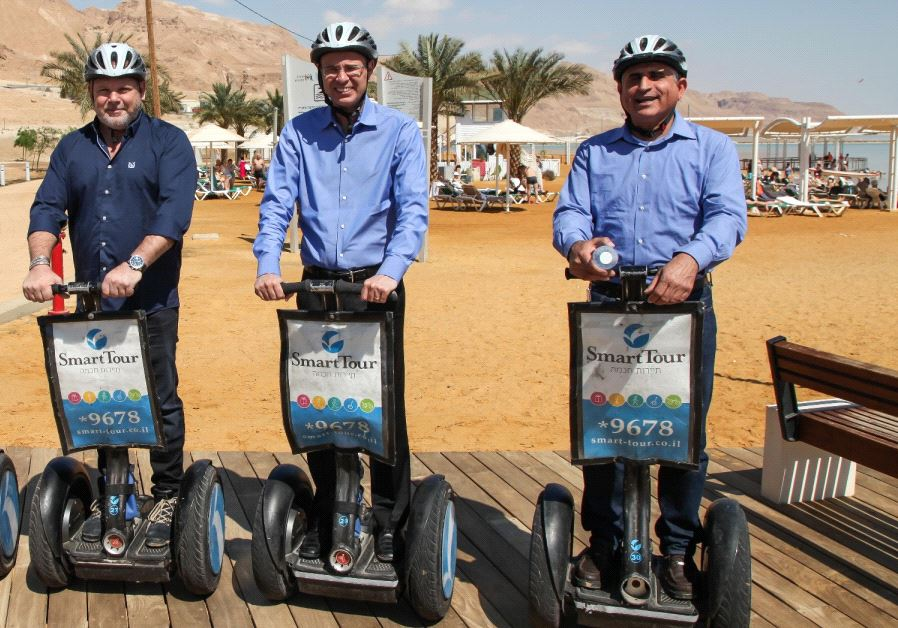 Tourism Minister Yariv Levin (center) rides a Segway off the coast of the Dead Sea.
