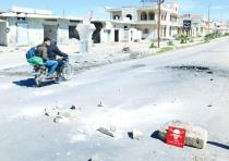 MEN RIDE a motorcycle yesterday past a hazard sign in rebel-held Khan Sheikhoun in Syria's Idlib pro
