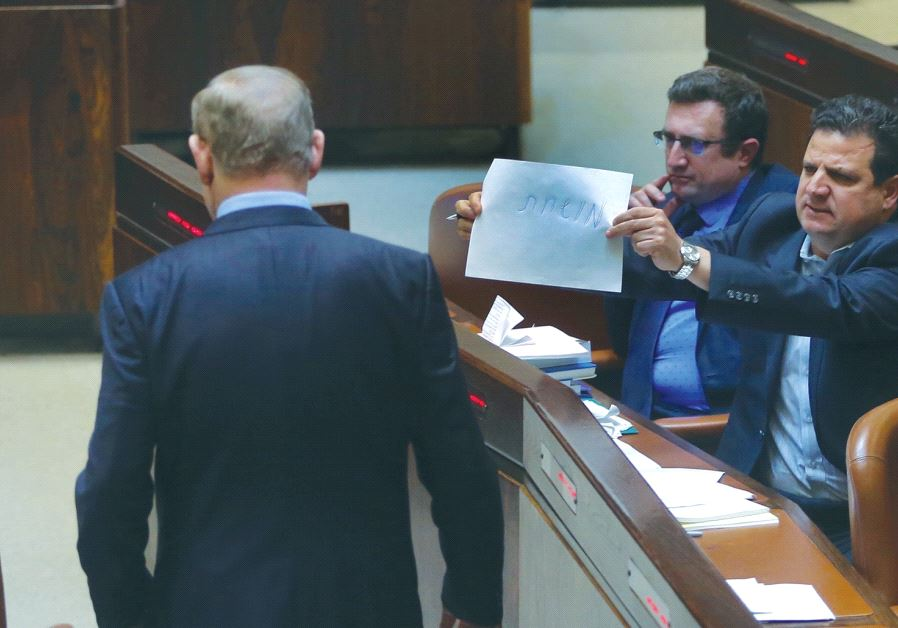 JOINT LIST chairman Ayman Odeh holds a piece of paper with the word 'corrupt' on it toward Prime Min