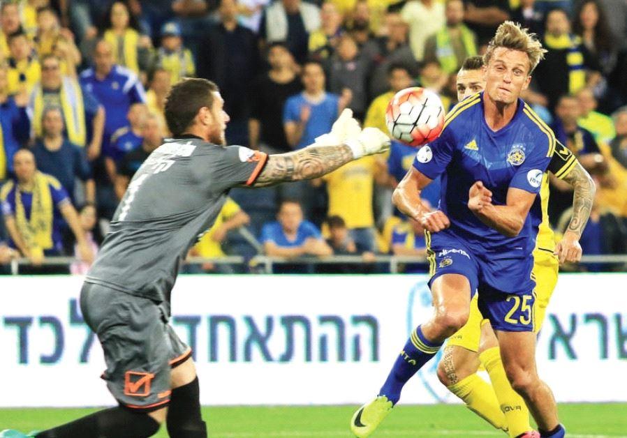 Maccabi Tel Aviv striker Aaron Schoenfeld (right) nets his team's opener in last night's 2-1 win ove