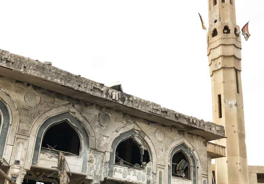 Shia militia flags hang from a mosque in Mosul