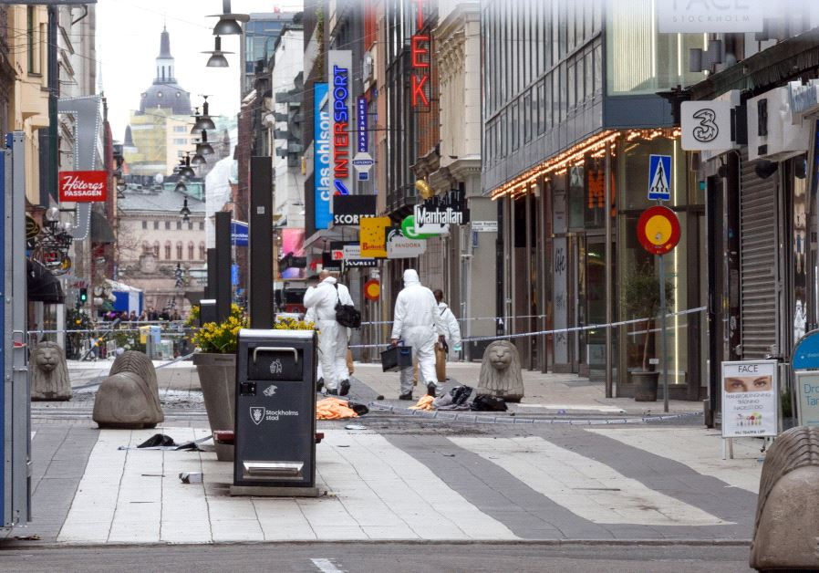 Forensic specialists walk to the crime scene in central Stockholm April 8, 2017.