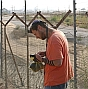 disengagement man prays next to fence 88