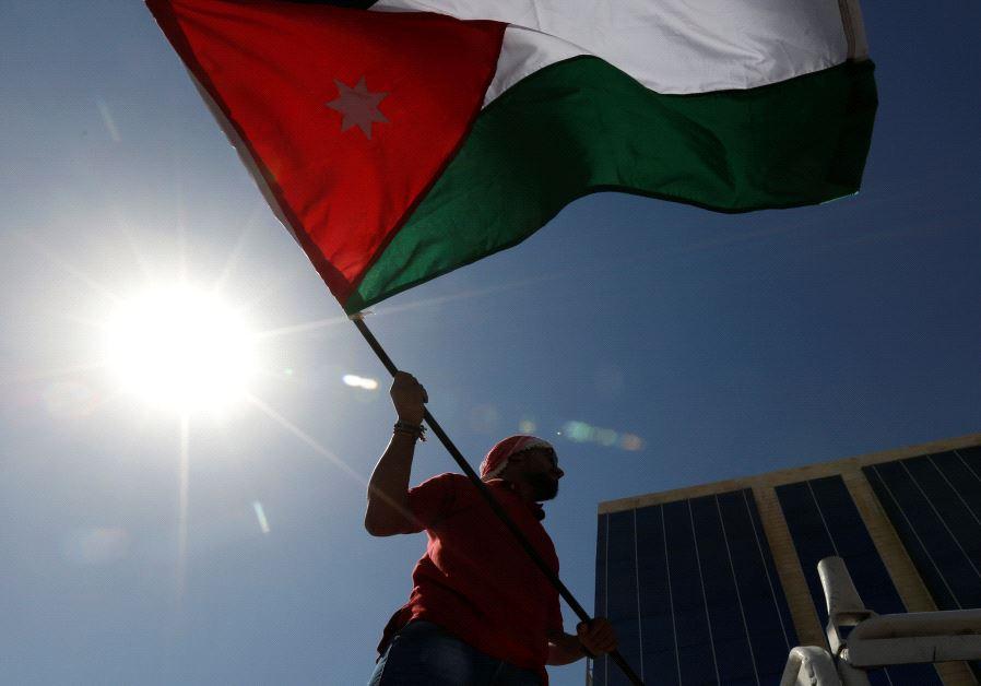 A Jordanian protester holds a Jordanian national flag