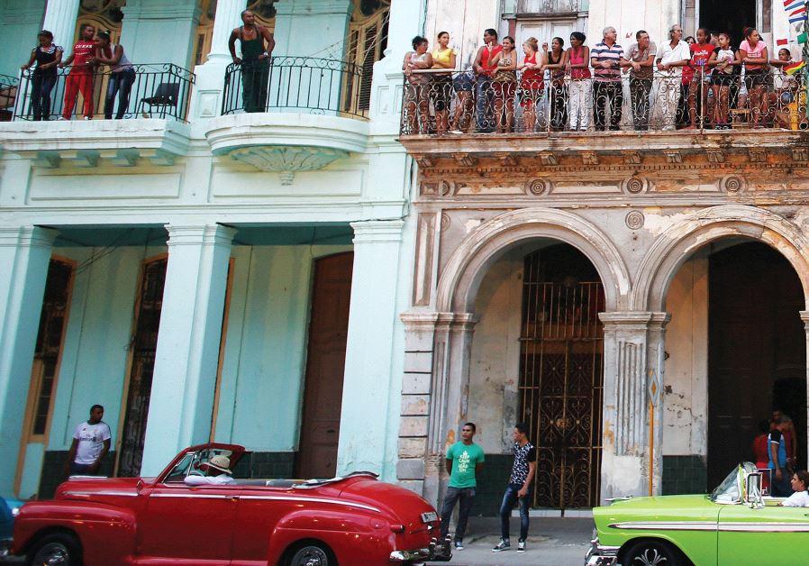 PEOPLE STAND on balconies on Paseo del Prado street in Havana, Cuba.