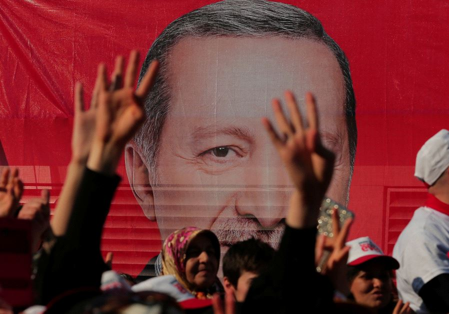 Supporters listen to the speech by Turkish President Tayyip Erdogan during a rally for the upcoming