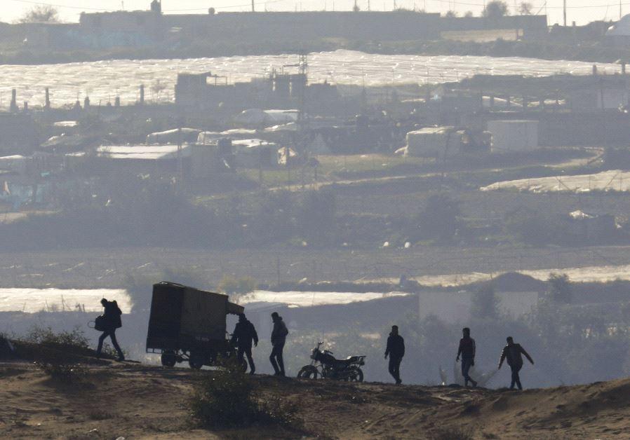 PALESTINIANS WALK near the Israel-Gaza border inside Gaza, where Hamas still holds Israeli citizens.