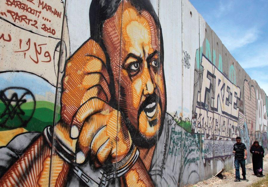 PALESTINIANS WALK past graffiti depicting jailed Fatah leader Marwan Barghouti, currently serving fi