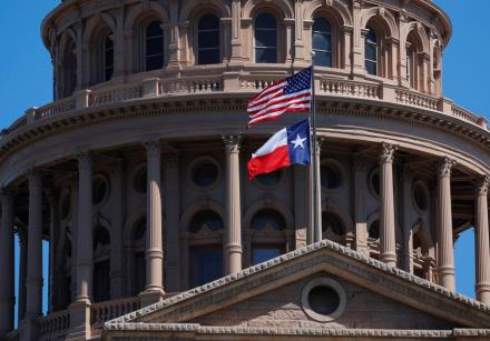 The US and Texas State flags fly over the Texas State Capitol in Austin