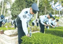 POLICE OFFICERS place flags on the graves of slain comrades at Mount Herzl in the capital yesterday