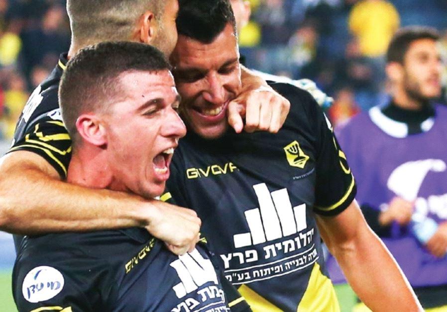 Beitar Jerusalem forward Idan Vered (front) celebrates with teammates after scoring a dramatic winne