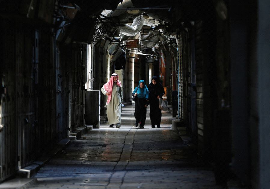 ARABS WALK passed closed shops in Jerusalem's Old City. 'Some 350,000 people – about one-third of Je