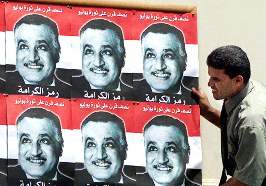 AN EGYPTIAN worker in 1967 mounts posters of president Gamal Abdel Nasser.