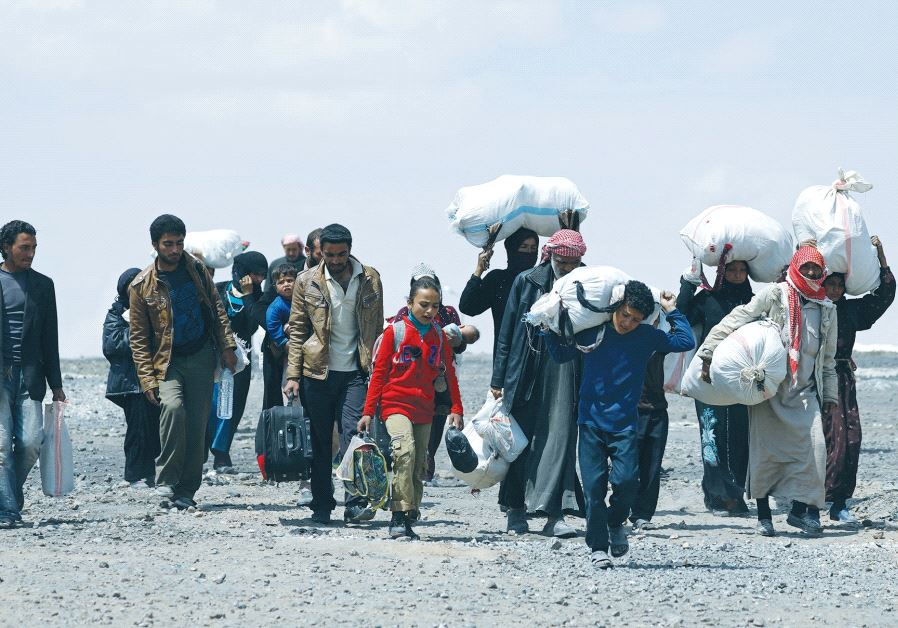 PEOPLE WHO FLED Raqqa city carry their belongings as they leave a camp in Ain Issa, in Syria.