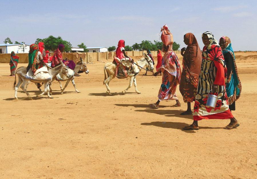 WOMEN WALK to the market in Abu Shock IDPs camp in Al Fashir, capital of North Darfur, Sudan.