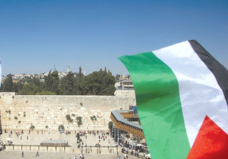 A Palestinian flag is seen waving in front of the Kotel