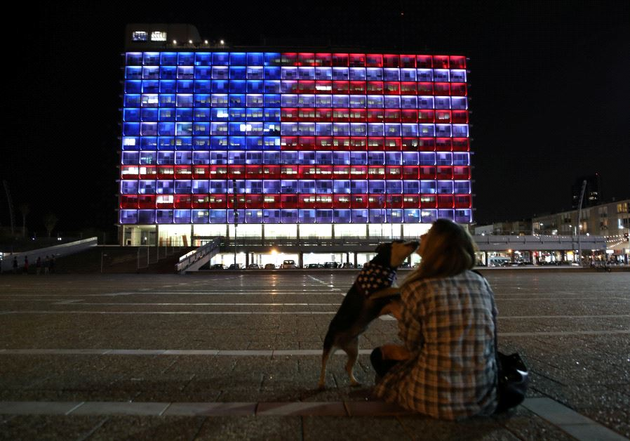 A woman plays with her dog as the municipality building is lit in the colours of the American flag on the first day of U.S. President Donald Trump's visit in Israel, in Tel Aviv, Israel May 22, 2017. REUTERS/Corinna Kern