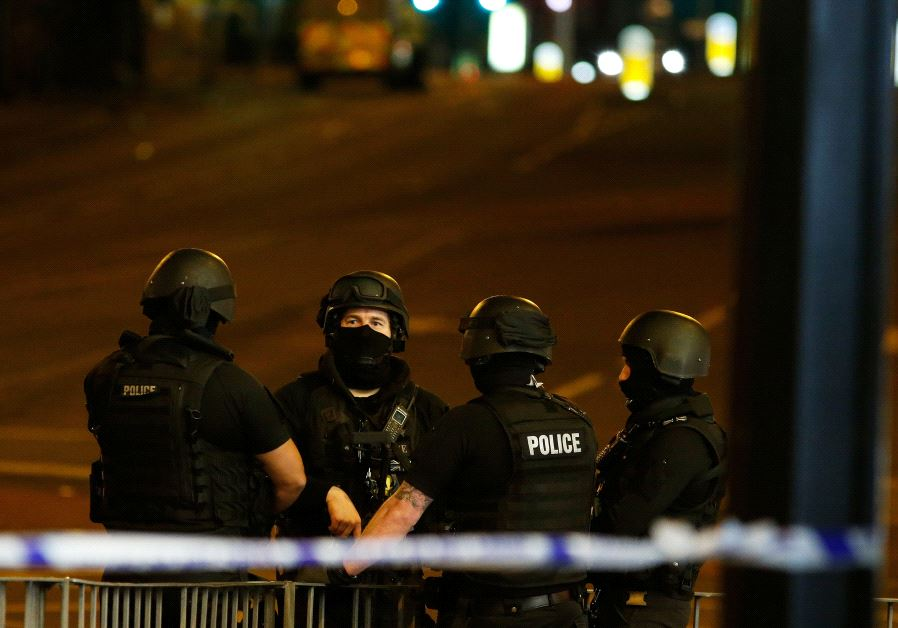 Armed police officers stand near the Manchester Arena, where US singer Ariana Grande had been perfor