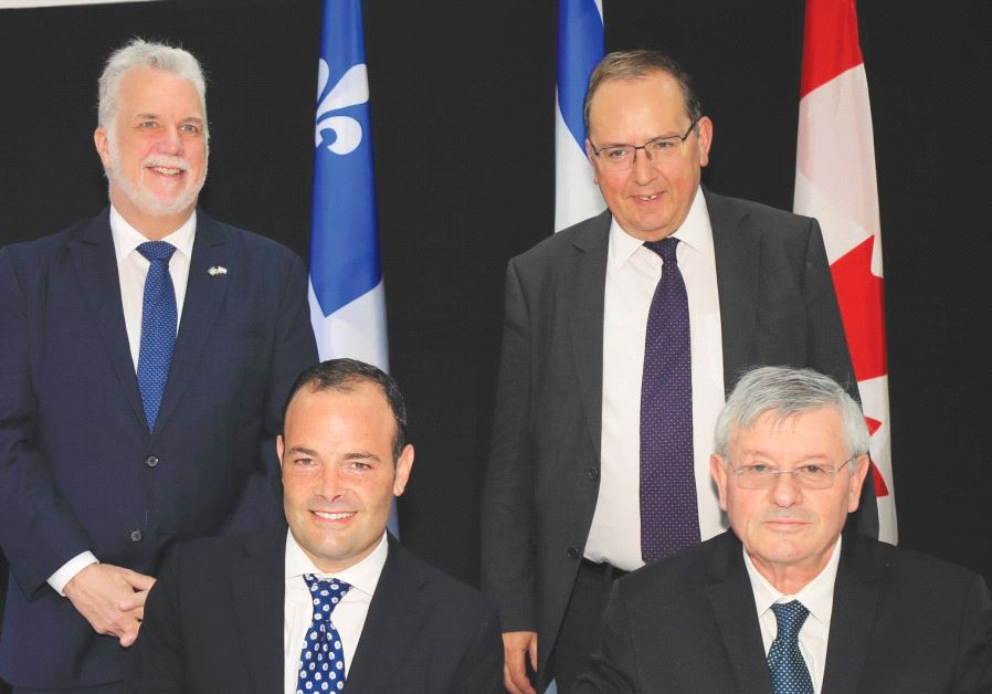 Israeli and Canadian businessmen signing an agreement.