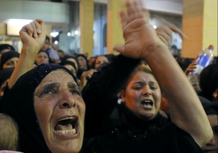 Relatives of victims of an attack that killed at least 28 Coptic Christians on Friday react at the f