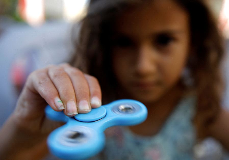 A girl performs tricks using a fidget spinner during a contest held in Ashdod, Israel May 11, 2017