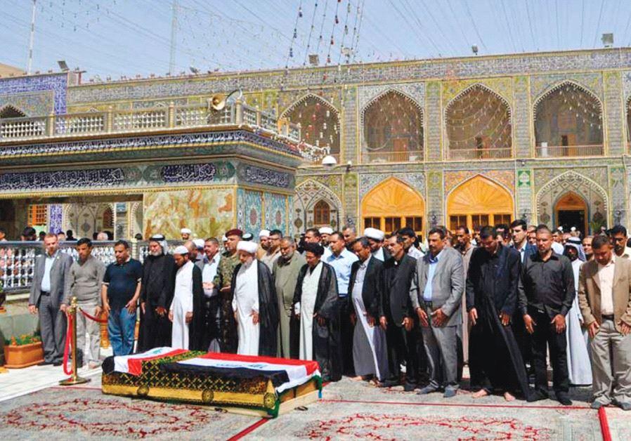 RESIDENTS PRAY near the coffin of Shaima Alawadi at the Imam Ali shrine in Najaf.