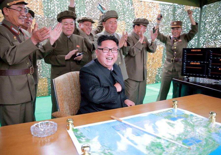 Kim Jong Un reacts during a test launch of ground-to-ground medium long-range ballistic rocket Hwaso