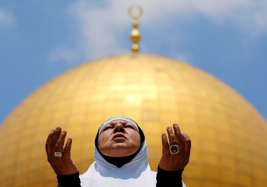 A Palestinian woman prays on the first Friday of the holy fasting month of Ramadan, at the Temple Mo