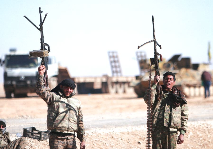 SYRIAN DEMOCRATIC Forces fighters hold up their weapons north of Raqqa city.