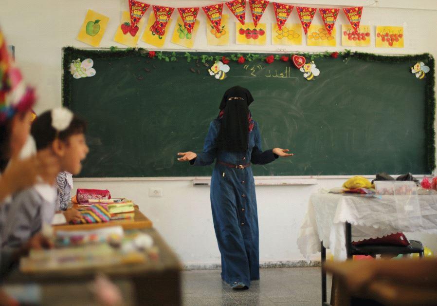 A PALESTINIAN TEACHER gestures as children attend a lesson at an UNRWA-run school in the Gaza Strip