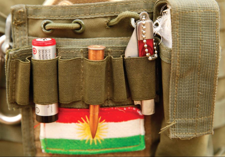 A BULLET and the Kurdistan flag are seen on a Peshmerga fighter's vest during a battle with ISIS.