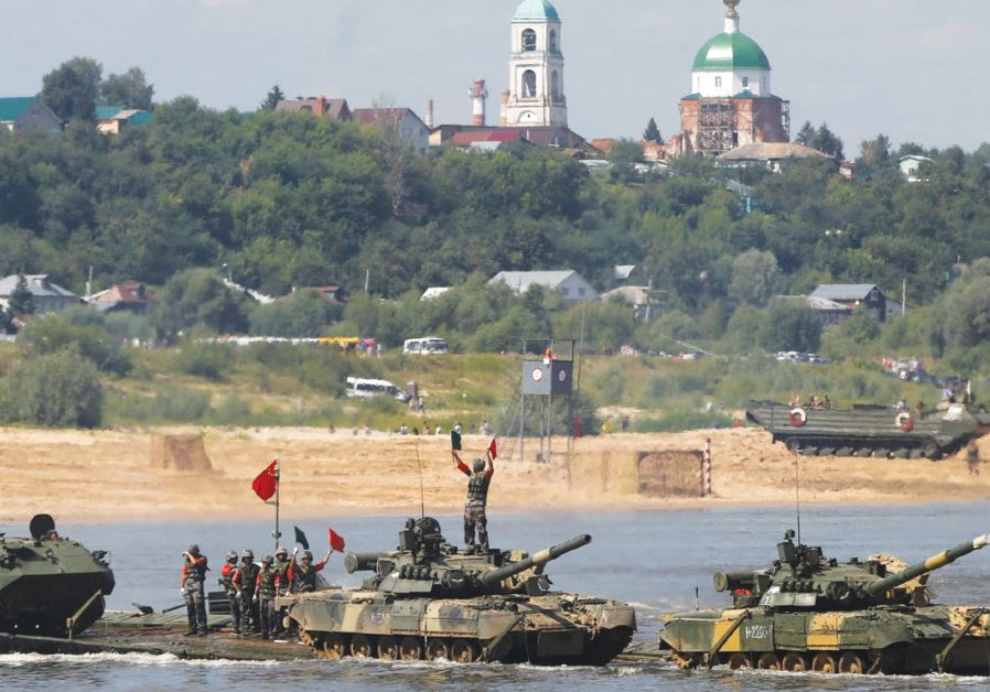 CHINESE CREW members transport T-80 tanks on a pontoon bridge during the Open Water competition for