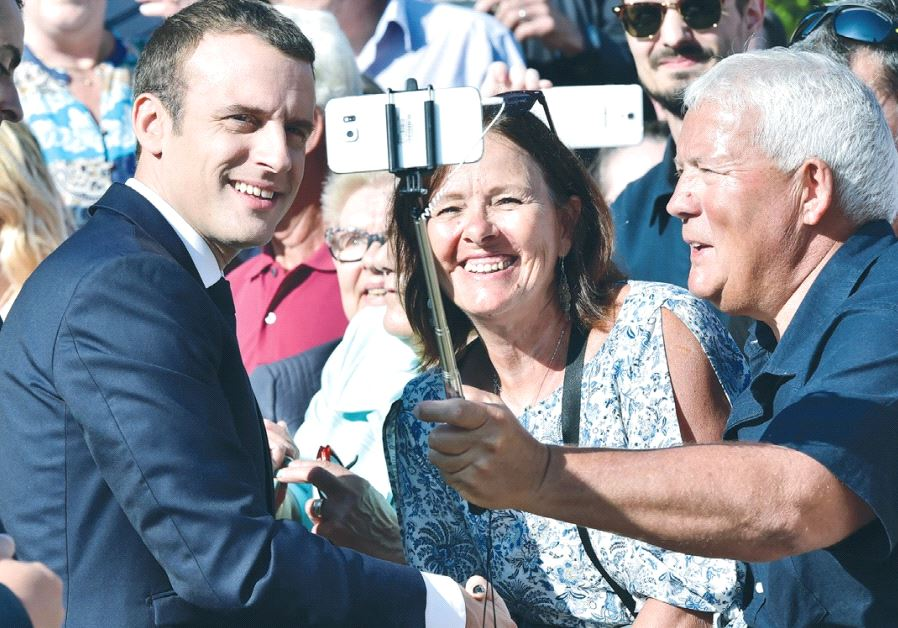 FRENCH PRESIDENT Emmanuel Macron (left) poses for a selfie after voting in the second round of parli