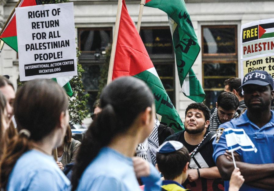 PEOPLE HOLDING Palestinian-rights placards taunt marchers in the Celebrate Israel Parade.