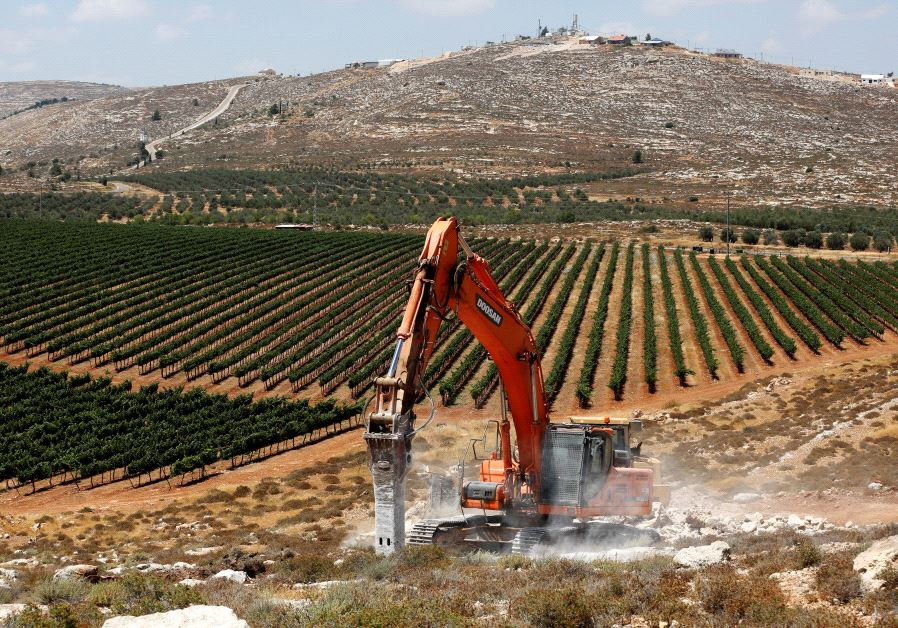 Heavy machinery work on a field as they begin construction work of Amichai, a new settlement.