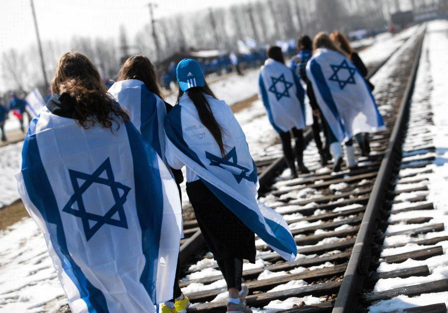 People wear Israeli flags around their shoulders inside Birkenau (Auschwitz II).