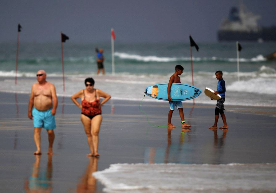 Youth holding surf boards chat as a couple walks along the shore of the Mediterranean Sea, Israel.